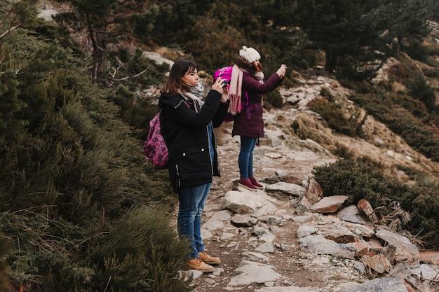 Zwei erfolgreiche wandererfreundinnen genießen die aussicht auf die bergspitze. glückliche wanderer in der natur, die fotos mit handy macht