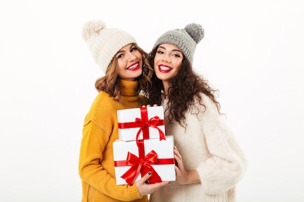 Zwei erfreute mädchen in den strickjacken und in hüten, die beim halten von geschenken über weißer wand zusammen stehen