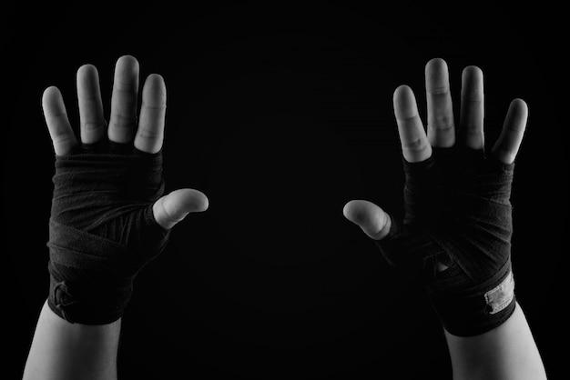 Zwei erhobene handflächen eines mannes, eingewickelt in einen schwarzen textilverband