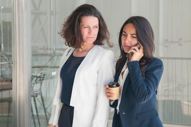Zwei ernste geschäftsfrauen, die um telefon ersuchen und kaffee trinken