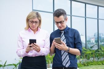 Zwei ernste Geschäftskollegen, die Telefone mit Stadtgebäudeglas verwenden