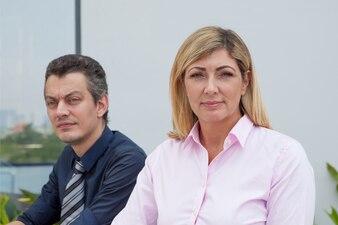 Zwei ernste männliche und weibliche Geschäftsleute von mittlerem Alter draußen.