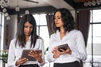 Zwei ernste weibliche Kollegen, die Geräte im Café verwenden.