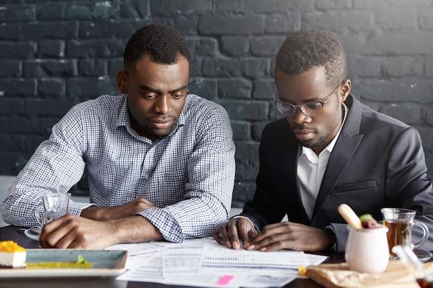 Zwei ernsthafte und konzentrierte afroamerikanische kollegen konzentrierten sich auf papierkram