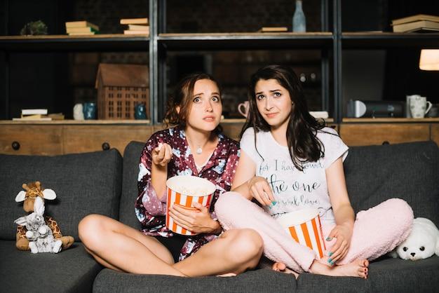 Zwei erschrockene frauen, die auf sofa mit popcorn aufpassendem fernsehen sitzen