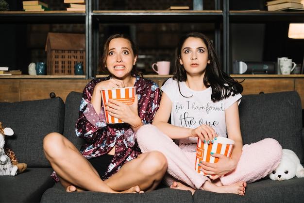 Zwei erschrockene weibliche freunde, die horrorfilm aufpassen