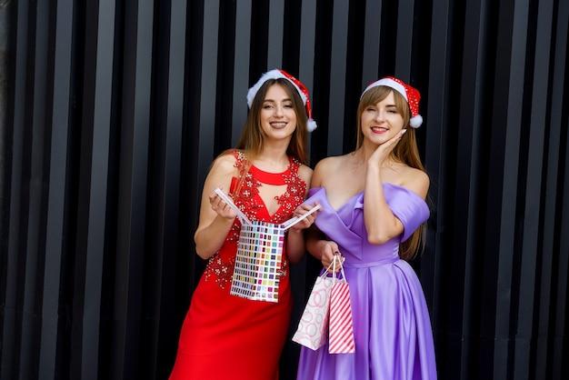 Zwei erstaunliche frauen in weihnachtsmützen und eleganten abendkleidern, die einkaufstaschen halten