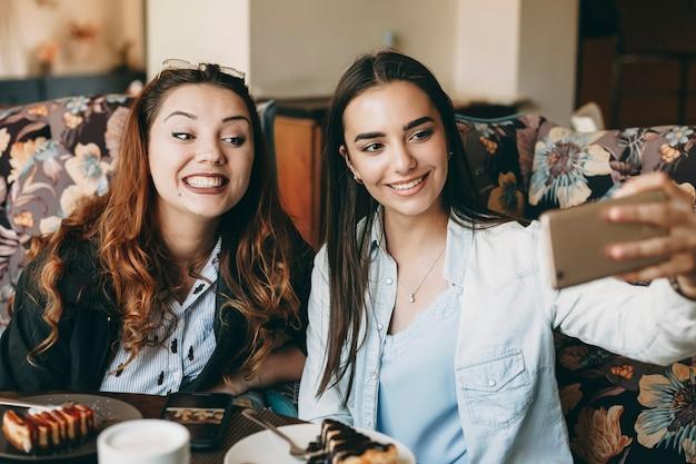 Zwei erstaunliche freundinnen, die spaß in einem café haben, das ein selfie auf dem smartphone nimmt, während sie kaffee trinken und einen kuchen essen.