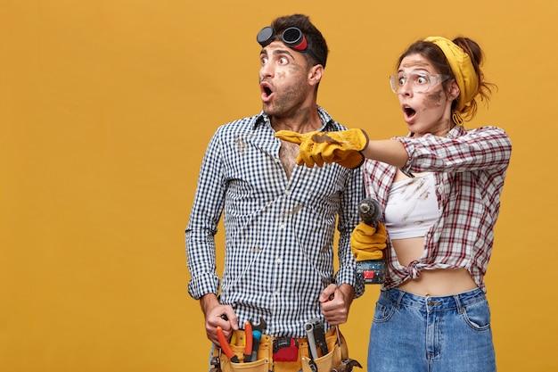 Zwei erstaunte elektriker mit schmutzigen gesichtern, die geschockt zur seite schauen: frau in schutzhandschuhen und schutzbrille, die ihren finger auf etwas zeigt. risiko, hochspannung, widerstand und gefahren bei der arbeit