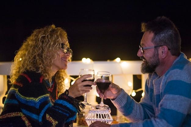 Zwei erwachsene aus ihrer beziehung gehen abends zum abendessen aus und essen zusammen - mann und frau klirren in einem restaurant