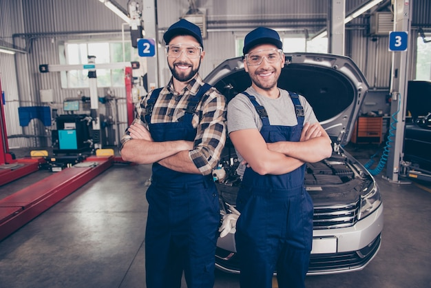 Zwei experten mit verschränkten armen lächeln in der kamera in einer speziellen sicherheitsausstattungsgarage