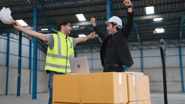 Zwei fabrikarbeiter feiern gemeinsam den erfolg in der fabrik oder im lager
