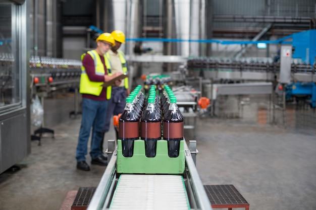 Zwei fabrikarbeiter überwachen kalte getränkeflaschen in der produktionslinie