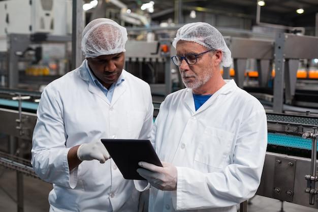 Zwei fabrikingenieure diskutieren über digitales tablet