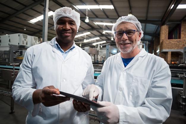 Zwei fabrikingenieure mit digitalem tablett lächeln in der getränkeproduktionsanlage
