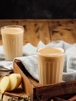 Zwei facettierte glasgläser auf einem holztisch mit dem traditionellen indischen getränk masala chai.