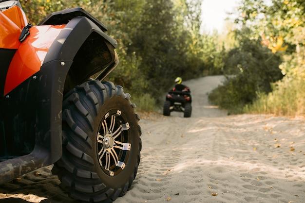 Zwei fahrer auf quads, die offroad-abenteuer im wald haben. fahren auf atv, blick vom lenkrad, extremsport und reisen