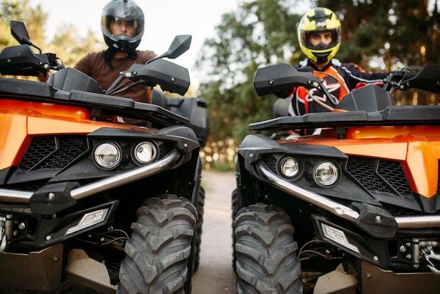 Zwei fahrer in helmen und ausrüstung auf quads, vorderansicht, nahaufnahme. männliche quadfahrer, atv-fahrer, extremsportler