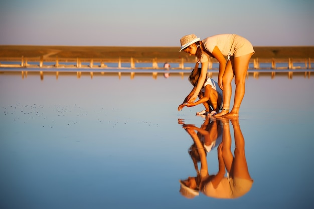 Zwei fantastisch schöne mädchen in ungewöhnlichen outfits an einem wunderschönen transparenten salzsee suchen etwas in einer glänzenden oberfläche