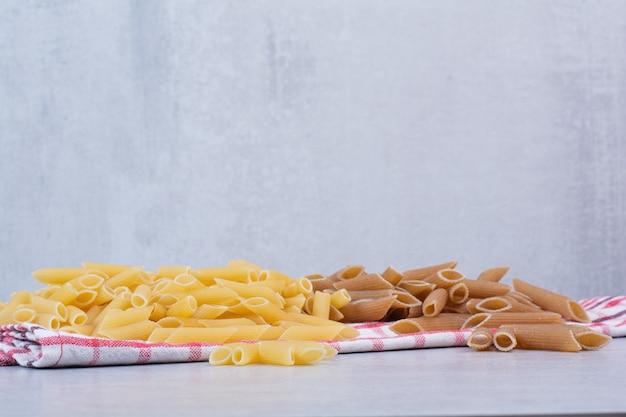 Zwei farben von rohen penne-nudeln auf gestreifter tischdecke