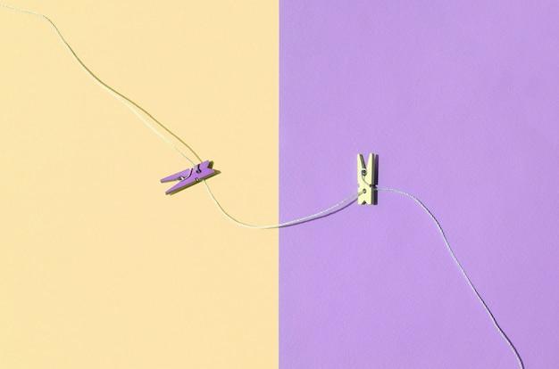 Zwei farbige hölzerne klammern und kleines seil liegen auf beschaffenheitshintergrund von gelben und violetten pastellfarben der mode