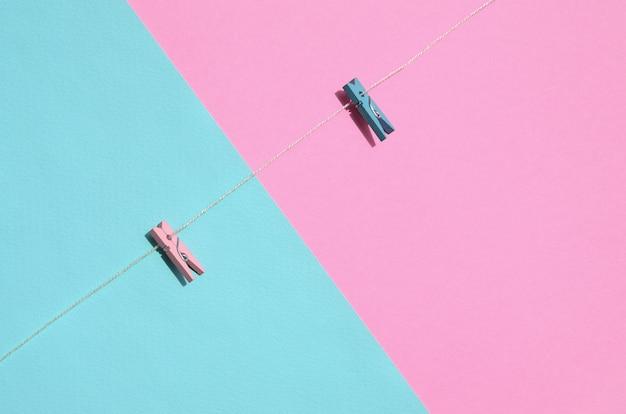 Zwei farbige hölzerne klammern und kleines seil liegen auf beschaffenheitshintergrund