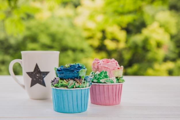 Zwei farbige muffins mit weißer schale mit stern auf weißem holztisch mit hellen grüns