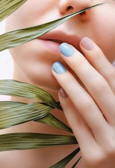 Zwei farbige nagelkunst und weibliche gesichtsnahaufnahme