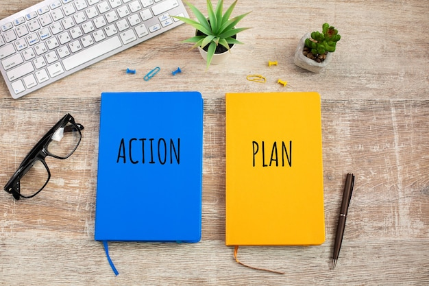 Zwei farbige notizbücher mit der aufschrift aktion und plan