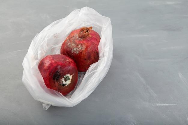 Zwei faule granatäpfel mit schimmel in einweg-plastiktüte