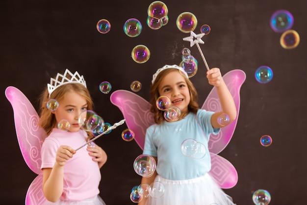 Zwei fee mit rosa flügeln und zauberstäben unter blasen.
