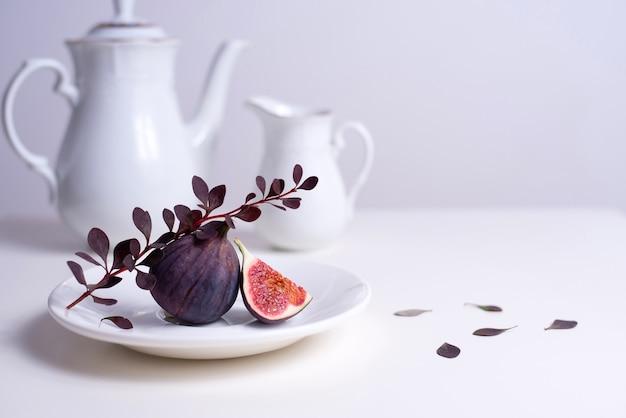 Zwei feigen auf einem weißen teller mit einem zweig berberitze, weißer teekanne und tasse auf dem tisch.
