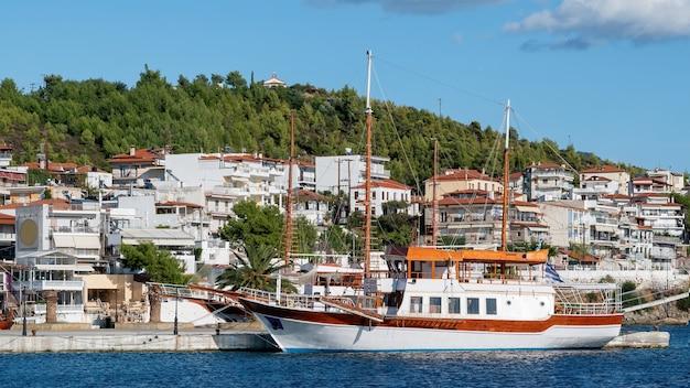 Zwei festgemachte segelboote in der nähe eines piers in neos marmaras, gebäude auf einem hügel mit viel grün, griechenland