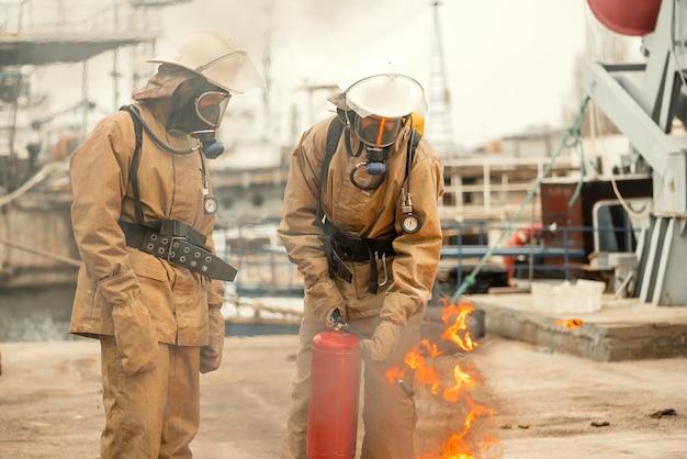 Zwei feuerwehrmänner in masken und ausrüstung bei einem training, wie man das feuer löscht