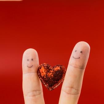 Zwei finger mit lächelnden gesichtern bemalt