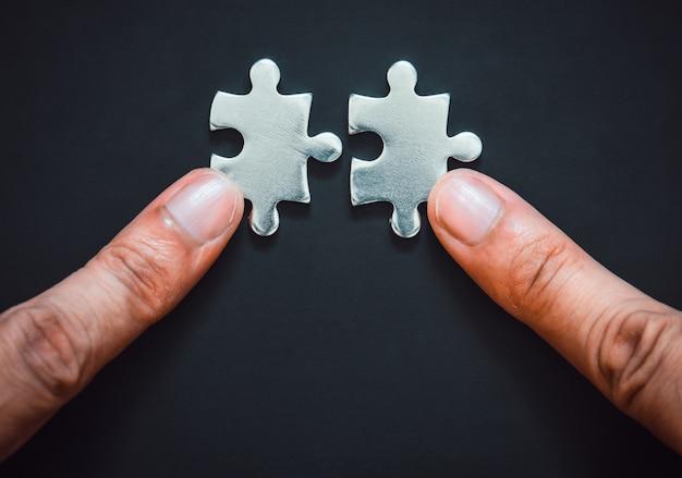Zwei finger verbinden teile des silbernen metallpuzzles