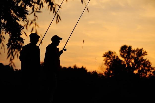 Zwei fischer bei sonnenuntergang. silhouetten von fischern