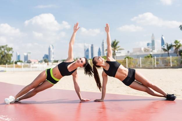 Zwei fitness junge frauen machen seitenplanke während übungen am strand