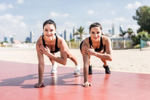 Zwei fitness-sportmädchen, die planken-sportübungen am strand machen