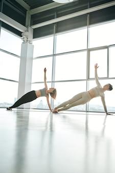 Zwei fitte mädchen in sportbekleidung, die mit ausgestreckten armen auf matten trainieren, während sie im freizeitzentrum gegen große fenster trainieren