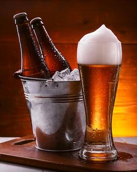 Zwei flaschen bier in einem eimer mit eis und ein glas bier mit üppigem schaum