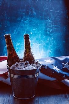 Zwei flaschen bier in einem eiskübel mit der amerikanischen flagge in der nähe. feierkonzept zum unabhängigkeitstag