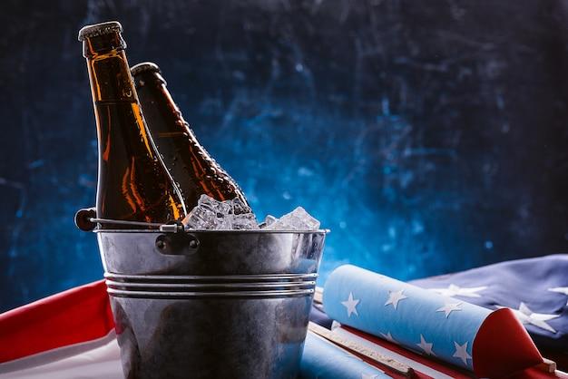 Zwei flaschen bier in einem eiskübel mit der amerikanischen flagge in der nähe und raketen für feuerwerk. feierkonzept zum unabhängigkeitstag