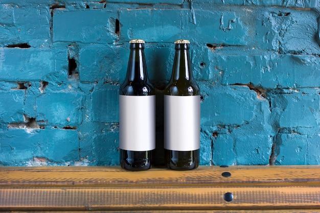 Zwei flaschen bier mit leeren aufklebern stehen auf einem hölzernen stand auf dem hintergrund einer backsteinmauer