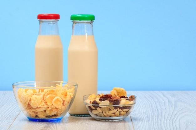 Zwei flaschen frische milch mit roter und grüner kappe, glasschalen mit müsli und cornflakes auf blauem hintergrund.