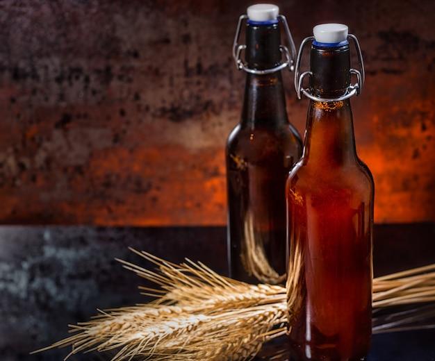 Zwei flaschen gefiltertes und ungefiltertes bier in der nähe von weizenzweigen auf einer schwarzen spiegeloberfläche. lebensmittel- und getränkekonzept
