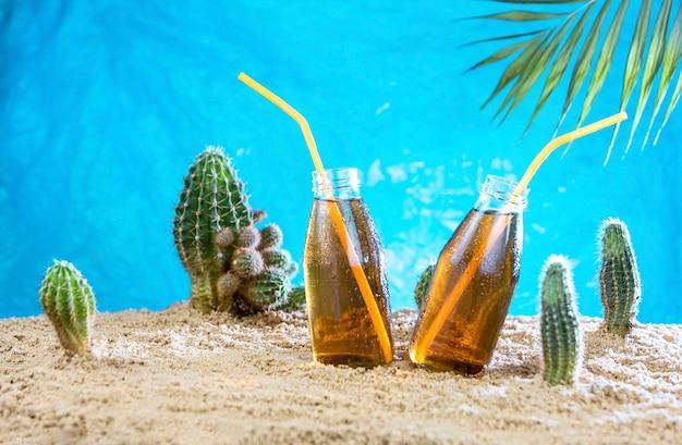 Zwei flaschen kambucha-cocktail auf dem sand mit kakteen