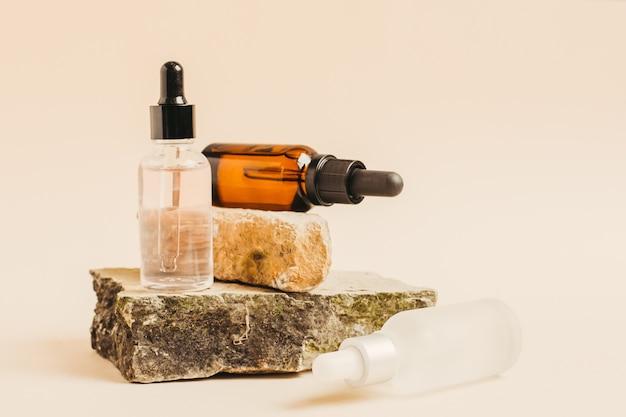 Zwei flaschen mit tropfen kosmetischer flüssigkeit, hyaluronsäure oder serum für die natürliche hautpflege