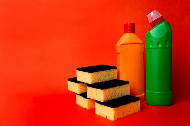 Zwei flaschen reinigungsmittel und reinigungsschwämme auf rotem grund