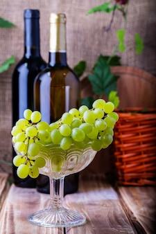 Zwei flaschen rot- und weißwein auf einem holztisch mit einer weintraube. selektiver fokus.